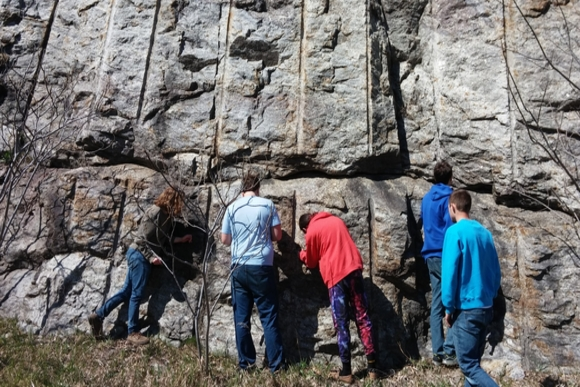 a group of students analyze a rock formation