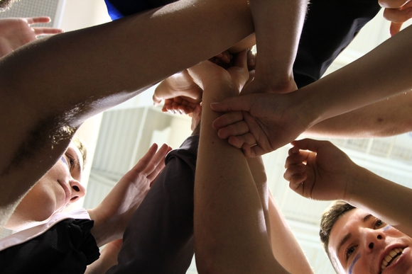 looking up from the floor at a huddle of athletes with their hands in for a cheer