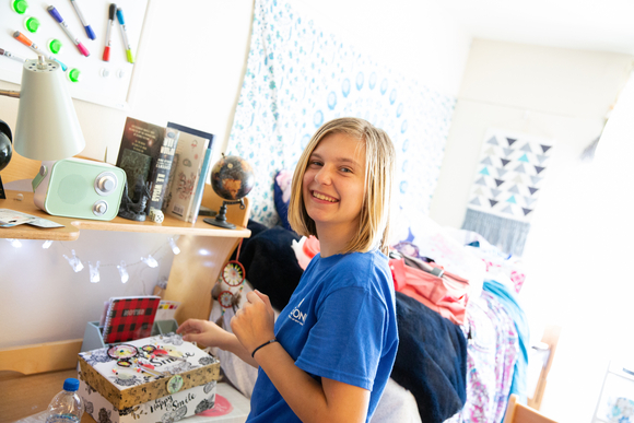 a student smiles as she moves into her residence hall during move-in weekend