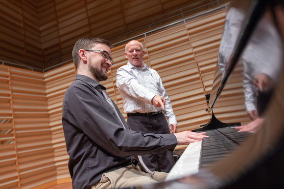 piano student with instructor in Rosch Recital Hall