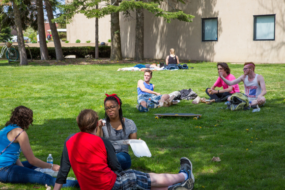 students sit in the grass and converse outside the Williams Center