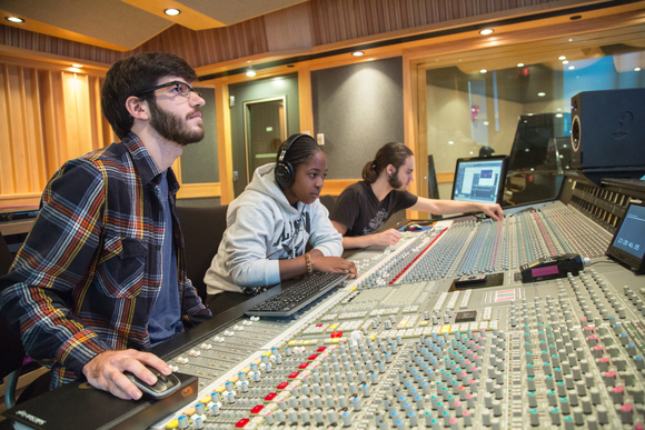 students listen to audio with headphones on in the sound recording studio