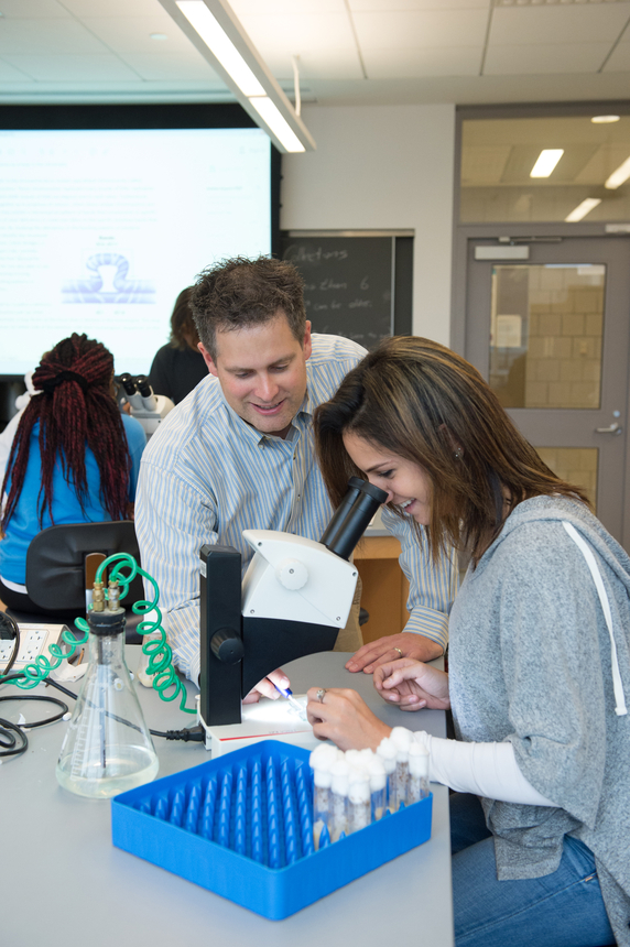 Biology Professor Scott Ferguson works with a student in a lab.