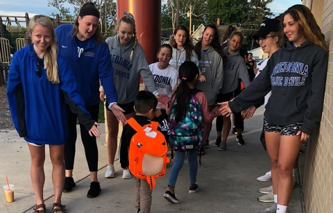 Student-athletes greet area youngsters on their way into school